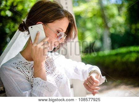 Woman With Cell Phone Looking Down At Watch