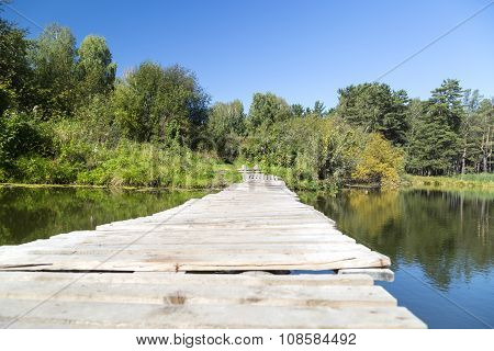 The old makeshift bridge connecting the two banks of a small lake