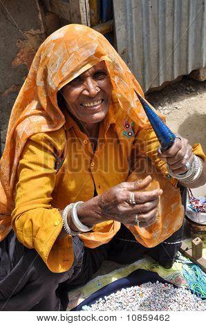 Elderly Lady In India Making Charm Bracelets