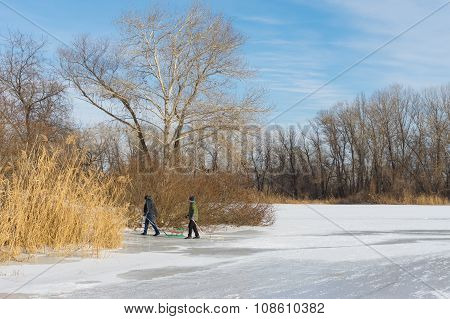 Children in the city use hilly bank of the frozen river Dnepr for to go in for sledging