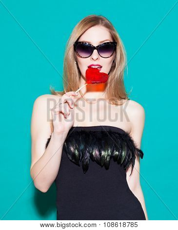 Fashionable Beautiful Girl Biting A Red Lollipop And Look At His. In A Black Dress On A Green Backgr