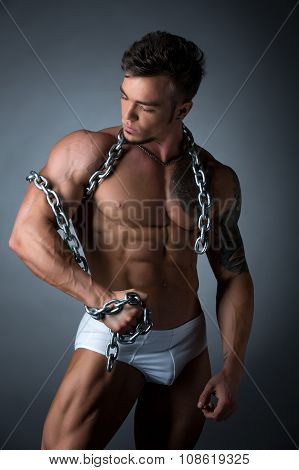 Hot muscular guy wrapped his biceps with chain