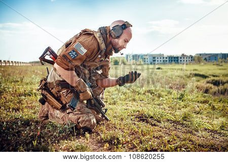 Military Pathfinder Is Looking At The Soil In His Hand. Ruined City On The Background.