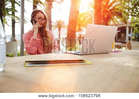 Smart female speaking on cell telephone while rest after work on laptop computer