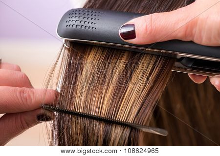 Hairstylist Straightening The Hair Of A Client
