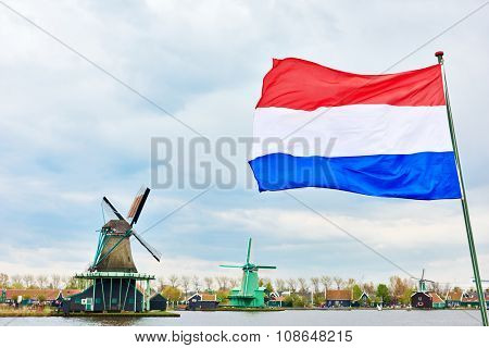 Flag of the Netherlands against traditional dutch windmill near  canal in Zaanse Schans