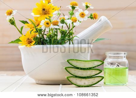 Alternative Health Care Fresh Herbal Aloe Vera , Oil And Wild Flower With Mortar On Wooden Backgroun