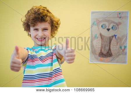 Boy holding his thumbs up and drawing beside him