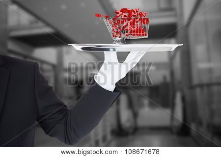 Hand with gloves holding a silver tray against online shopping concept