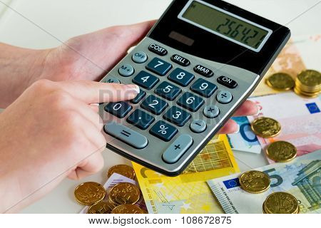 hand with calculator and bills. symbolic photo for sales, profits, taxes, and costing
