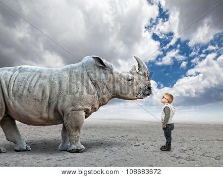 little child and huge rhino with abstract background