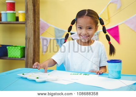 Smiling girl who is finger painting at the desk