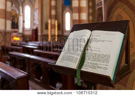 ALBA, ITALY - MAY 11, 2015: Open Bible on the stand inside San Lorenzo Cathedral (aka Duomo) - biggest and one of the important cathedrals in town of Alba dedicated to Saint Lawrence.