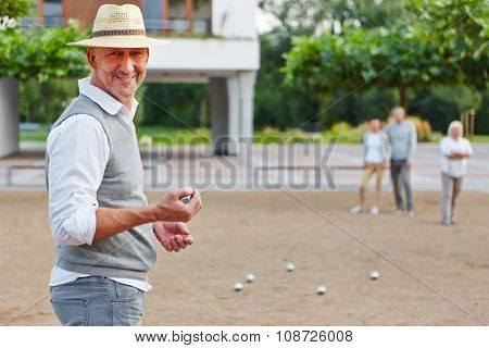 Smiling old man with ball for boule game in a city