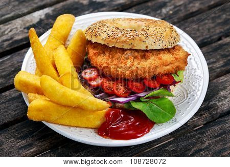 Home made Chicken burger with fried potatoes on old wooden table. poster