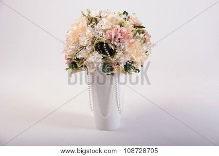 Artificial flowers bouquet in the vase isolated on white