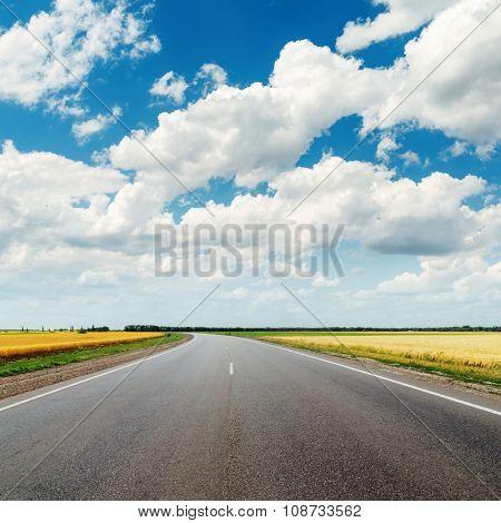 asphalt road to horizon and cloudy sky