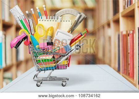 Stationery objects in mini supermarket cart on  background