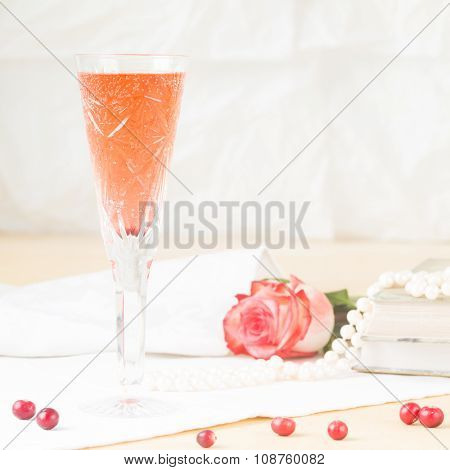Glass Of Kir Royal Cocktail With Vintage Books And Pearls