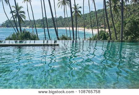 Eternity swimming pool above sandy paradise beach and palm trees in tropical landscape. poster