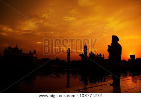 Silhouette of Sikh prayer at golden temple, Amritsar, India
