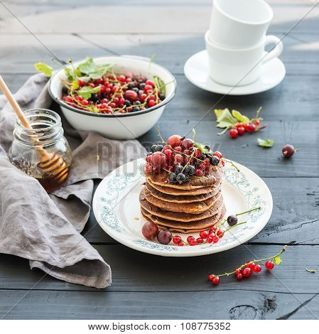 Breakfast set. Buckwheat pancakes with fresh berries and honey on rustic plate over black wooden