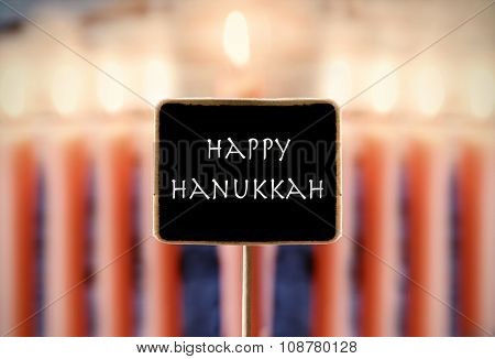 closeup of a chalkboard with text happy Hanukkah and a menorah with nine lit candle in the background