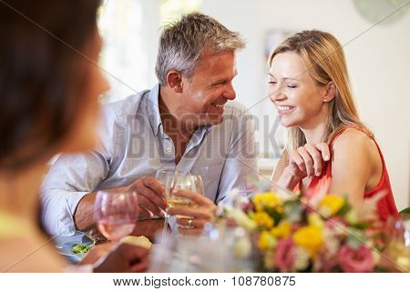 Mature Couple Sitting Around Table At Dinner Party