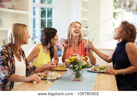 Mature Female Friends Sitting Around Table At Dinner Party