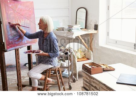 Female Artist Working On Painting In Studio