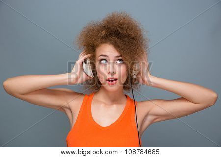 Portrait of young pretty curly amusing woman in orange top thinking and listening to music with headphones poster