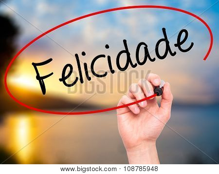 Man Hand writing Felicidade (Happiness in Portuguese) with black marker on visual screen.