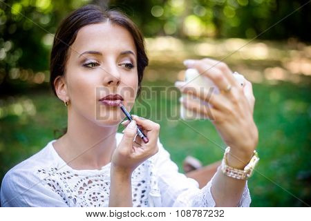 Pretty Woman Applying Lipstick At The Garden