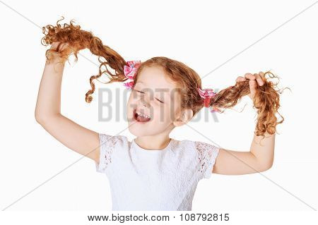 Laughing girl pull her pigtails up by hand and sing son in light background.