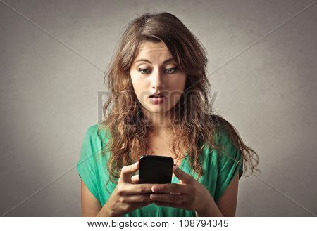 Spellbound girl staring at her phone