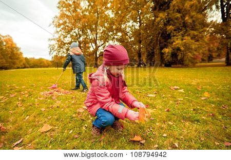 childhood, leisure, friendship and people concept - little girl and boy with rack collecting and racking leaves in autumn park poster