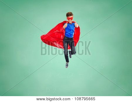 education, gesture, childhood, and people concept - boy in red super hero cape and mask flying in air and showing thumbs up over green school chalk board background