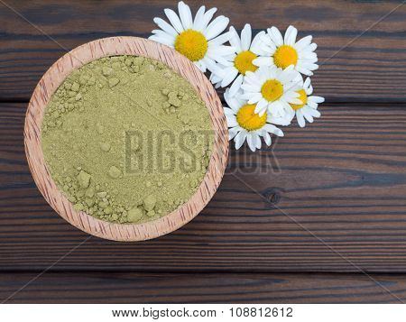 Henna Powder In The Coconut Bowl And Chamomile Flowers