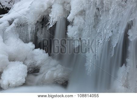 Cripple (stream) covered with frost and icicles. Water current is like to woman's hair. poster