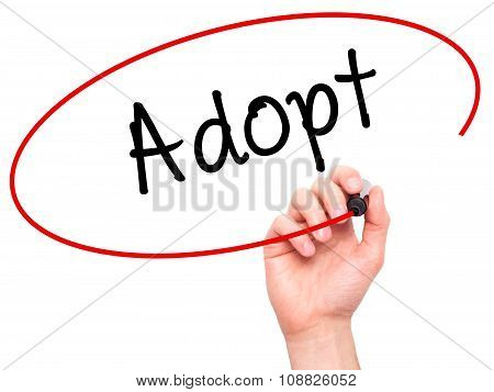 Man Hand writing Adopt with black marker on visual screen.