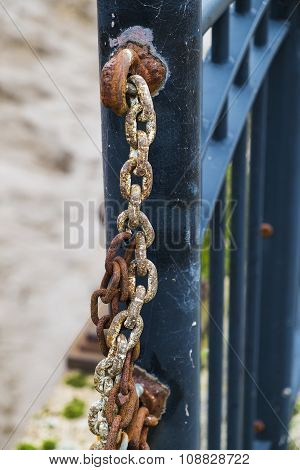 close up of rusted chain attached to metal fence poster