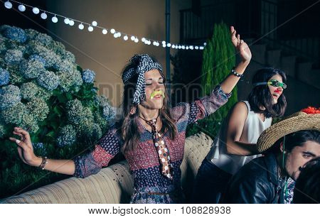 Portrait of beautiful young woman with funny moustache and necktie dancing and having fun in a outdoors party. Friendship and celebrations concept. poster