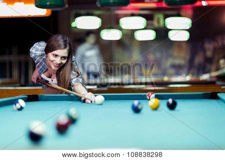 Young beautiful young lady aiming to take the snooker shot while leaning over the table in a club poster