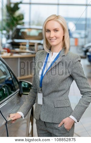 Sales representative is about to open a car door.