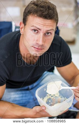 Hungry muscular shirtless man gulping down food