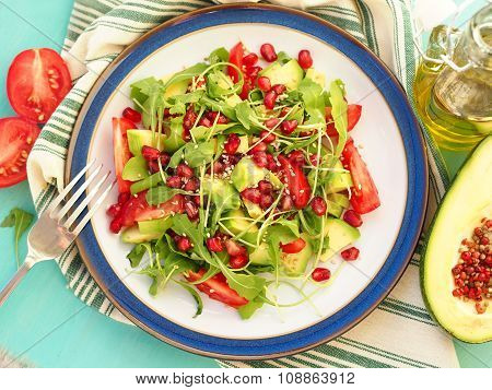 Vegetarian salad with avocado tomato wedges rucola leaves pomegranate and sesame seeds poster