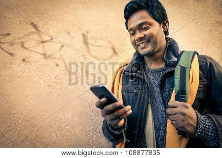 Young Indian Man Holding Mobile Phone - Cheerful Asian Model Next To Old Urban Wall - Soft Vintage F