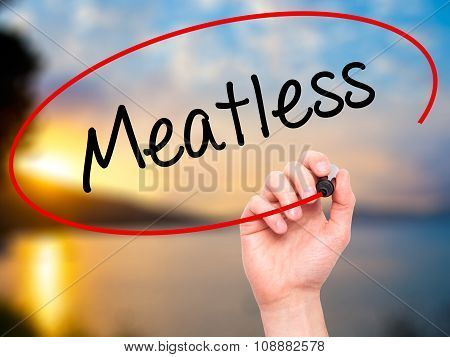 Man Hand writing Meatless with black marker on visual screen.