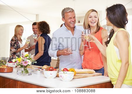 Mature Guests Being Welcomed At Dinner Party By Friends