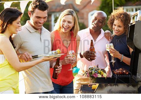 Mature Friends Enjoying Outdoor Summer Barbeque In Garden